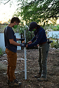 Watershed Management Group staffers Charlie Alcorn and Nichole Casebeer setting up a laser level.