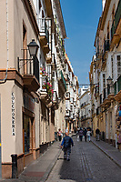 Colchoneria road in Cadiz, Spain is a narrow pedestrian street with three-story buildings along the cobblestone walkway.