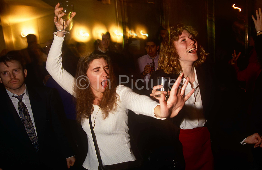 A young woman dances and sings with friends and associates during a karaoke night at a City of London wine bar. Holding high a glass of an unknown drink, she shouts out the words during this evening of after-work merriment where friends and associates gather to share alcohol and fun.
