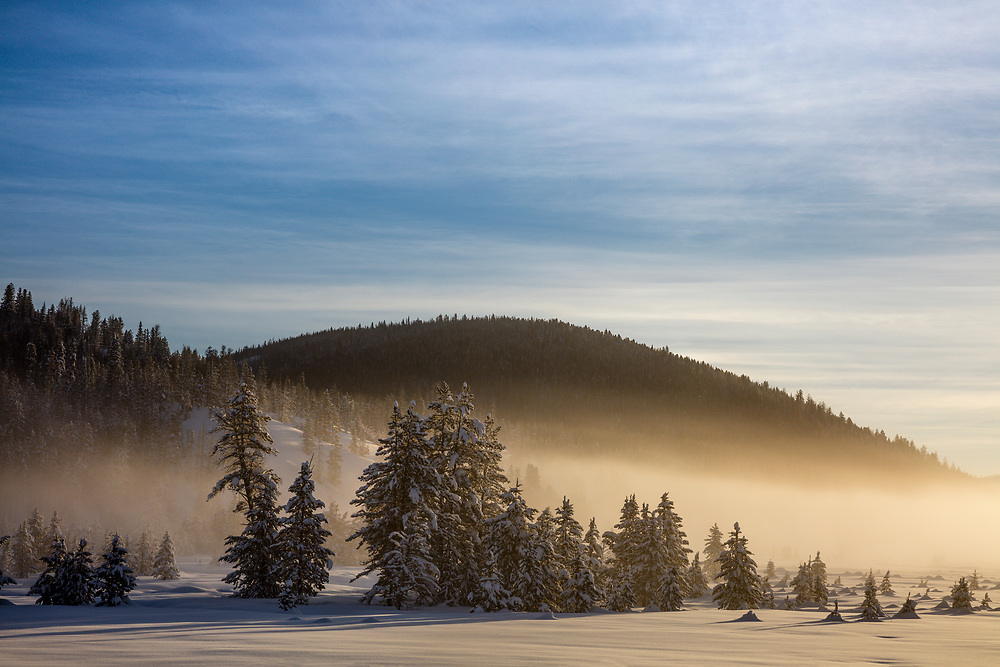 Winters morning fog and mist lift at sunrise in the Sawtooth Valley near Stanley in Central Idaho with a deep blanket of snow covering the land. Licensing and Open Edition Prints.