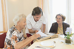 Caregiver watching photo album with senior women at rest home, Bavaria, Germany