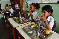"""Ana Cecilia Yamusa(right) , Dugleymis Martinez(next to Ana) and other students say grace in their 1st grade classroom at the Florencio Jimenez school.  The school is one of the new """"Bolivarian"""" Schools which are part of President Chavez's Education Reform.  The new Bolivarian Schools keep students for an entire day, as opposed to a half day, feed the students lunch and offer programs like drama, art and music. While President Chavez touts his programs that benefit the poor, many point to a rising poverty rate and shrinking economy and claim the programs fail to substantially help.  ."""