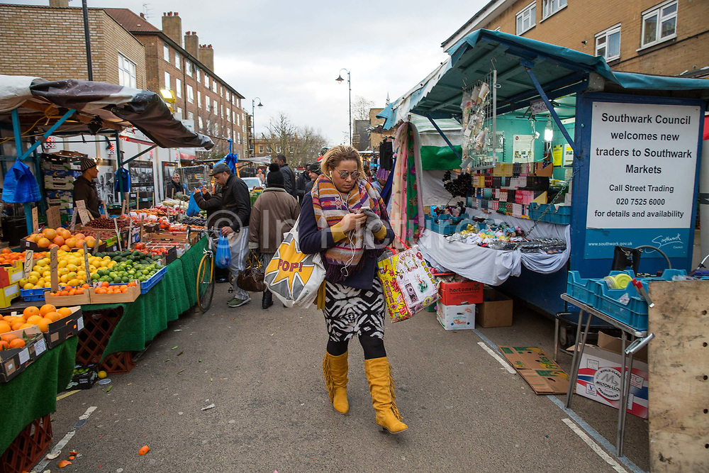 A young woman in colourful clothes checks her mobile phone walking through East Street Market on 11th January 2017 in London, United Kingdom. East Street Market also known locally as The Lane, or East Lane, is a busy street market in Walworth in South London. It is large and vibrant and is good for African and Caribbean fruit and vegetables, material and household goods. From the series Our Small World, an observation of our mobile phone obsessions