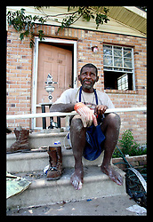 29 August 2006 - New Orleans - Louisiana. Lower 9th ward. On the one year anniversary of hurricane Katrina, and most of the area remains derelict and abandoned. Resident Terry Charles moved back into his flood ravaged home months ago and lives in his mould filled home from which he was lucky to escape when the hurricane hit. Terry suffers from severe mental problems, yet somehow manages to live alone with no neighbours or community. He has not eaten for days. He holds a net he made, in which he 'catches things.' The net contained a flood damaged rusty cigarette lighter and various bits of junk. There are no social services to help Terry. He can quote passages from the bible and scratches bizarre drawings on bits of paper he finds. Terry needs help desperately, but none is available to him. He does not know it is the one year anniversary today.