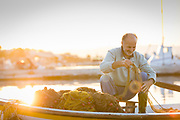 Smiling fisherman checking fishing net on boat moored in harbor at sunrise, Skala Kallonis, Lesbos, Greece
