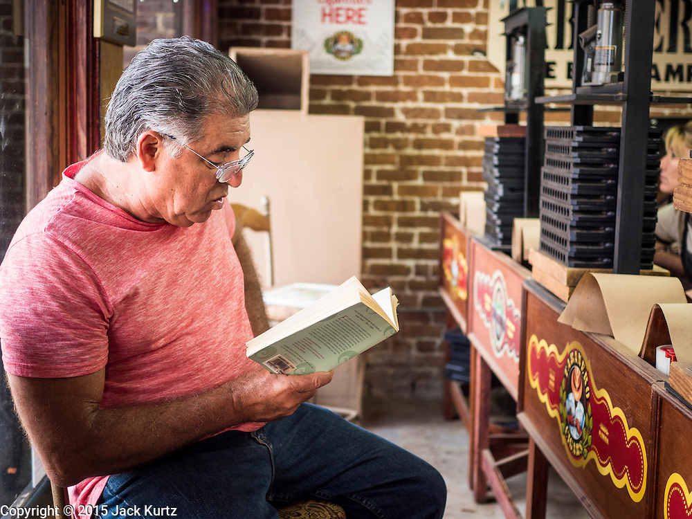 """30 APRIL 2015 - TAMPA, FLORIDA, USA: A """"reader"""" at Tabanero Cigars, a cigar factory and coffee house in the Ybor City section of Tampa, FL. Readers are traditionally found in Cuban cigar factories. They read books and newspapers to the workers who roll cigars. Tabanero Cigars handrolls cigars in the traditional Cuban style. Most of the rollers at Tabanero have immigrated to the US from Cuba. Ybor is a historically Cuban immigrant community that has been redeveloped and gentrified into a popular tourist destination lined with cigar factories, boutiques and cafes.     PHOTO BY JACK KURTZ"""