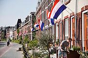 Nederland, Nijmegen, 27-4-2020  De bewoners van de nijmeegse nieuwbouwwijk Koningsdaal kregen bij oplevering van hun huis allemaal een vlag en oranje wimpel. Die hangen ze nu met Koningsdag, woningdag, massaal uit . Vanwege de coronacrisis blijft elk gezin op zijn eigen stoepje bij de voordeur hangen .Foto: Flip Franssen