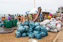 © Licensed to London News Pictures. 04/08/2019. Brighton, UK. Members of the public take part in the beach clean the day after the Brighton and Hove Pride Saturday. Dozens of bags of bottles, cans and plastic are collected from the Seaside resort beach. Photo credit: Hugo Michiels/LNP