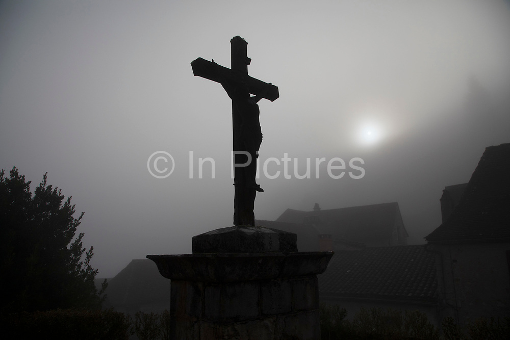 Crucifix in silhouette as the sun shines through the mist St Cirq-Lapopie, France. Saint-Cirq-Lapopie is a commune in the Lot department in south-western France. It is a member of the Les Plus Beaux Villages de France The most beautiful villages of France association. Its position, originally selected for defense, perched on a steep cliff 100 m above the river has helped make the town one of the most popular tourist destinations in the department.