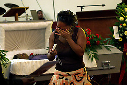 04 August 2006. New Orleans,  Louisiana. .Funeral for victims of Homicide, New Home Baptist Church. Friends and relatives of three young men gunned down late at night on a city street on July 28th pay their respects. 4 men were gunned down that night in one incident as crime spirals out of control in New Orleans. Three of the victims, all brothers buried today are Kadeem Stephen (16yrs), Kendall Stephen (21yrs) and Kareem Stephen (also 16yrs). One of the victims sisters (name unknown) is overcome with grief..Photo; Charlie Varley..