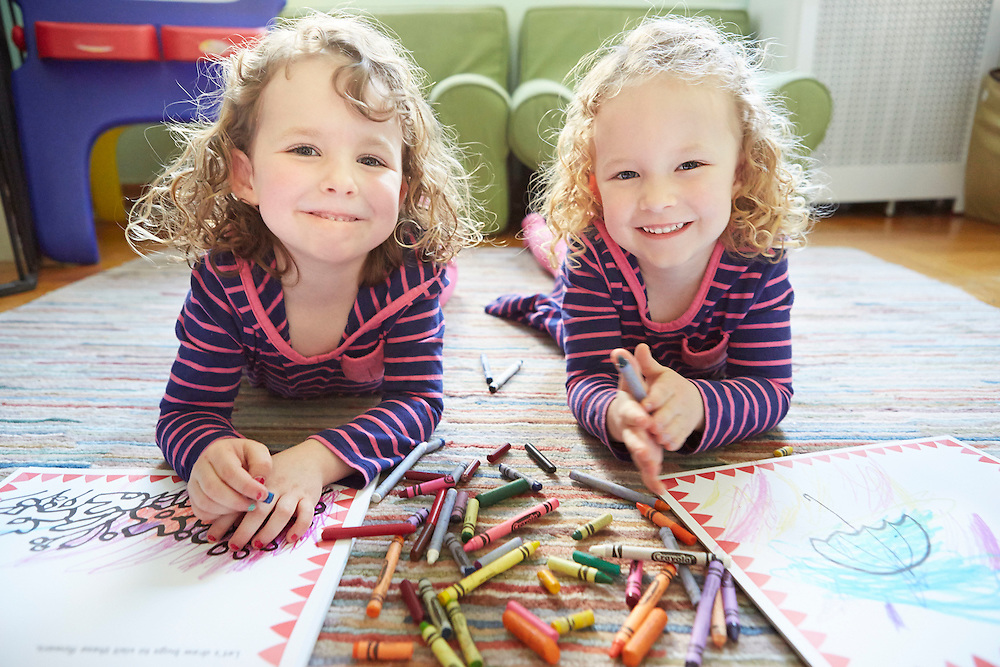 Twins playing with crayons and coloring books at home
