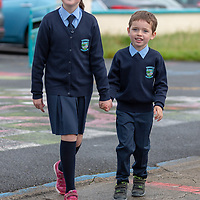 Junior Infant Jamie Sugrue and his big sister Chloe walks into school on their first day back on Thursday morning