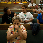 San Bernardino residents who lined up for free food pray for better times at Second Chance Ministry. People received one bag of USDA food and a second bag of food donated directly from the church if they stayed for a church service.