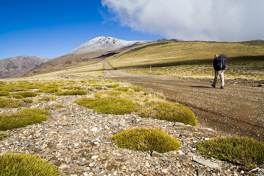 A backpacker hikes the trail to Mulhacen, visible dusted in snow in the distance, Sierra Nevada National Park, Andalusia, Spain. Mulhacen is the highest mountain in continental Spain and in the Iberian Peninsula.