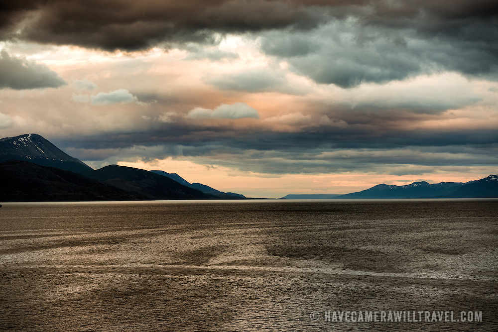 Heavy clouds capture the dusk light in the Beagle Channel along southern Argentina and Chile. The channel is named after the ship that transported Charles Darwin on his famous expedition to the Galapagos Islands. On the way home, they explored and named the channel through the islands at the southern tip of the continent.