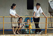 """A North Korean family on a boat in the river port town of Sinuiju July 8, 2006. China and North Korea are separated by the Yalu River, upon which Chinese tourists take pleaure cruises across the water to  observe their less economically developed neighbors.  North Korea has threatened to take """"stronger physical actions"""" after Japan imposed punitive measures in response to its barrage of missile tests and pushed for international sanctions. North Korea has vowed to carry out more launches and has said it will use force if the international community tries to stop it. DPRK, north korea, china, dandong, border, liaoning, democratic, people's, rebiblic, of, korea, nuclear, test, rice, japan, arms, race, weapons, stalinist, communist, kin jong il"""