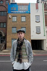 © Licensed to London News Pictures.04/13/2013. London, UK. Artist Alex Chinneck stands in front of his Upside Down House on Blackfairs Road, London. The London-based artist has taken a building on Blackfriars Road, due for demolition, and turned its façade upside down with a design that considers and celebrates the history and life of the building.Photo credit : Peter Kollanyi/LNP