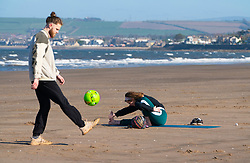 Portobello, Scotland, UK. 18 April 2020. Views of the Portobello promenade and beach on a sunny but cld and windy Saturday afternoon during the coronavirus lockdown in the UK . Woman does yoga while partner plays football.  Iain Masterton/Alamy Live News