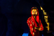 """19th March 2015, New Delhi, India. A woman illuminated by a shaft of sunlight in the ruins of Feroz Shah Kotla in New Delhi, India on the 19th March 2015<br /> <br /> PHOTOGRAPH BY AND COPYRIGHT OF SIMON DE TREY-WHITE a photographer in delhi<br /> + 91 98103 99809. Email: simon@simondetreywhite.com<br /> <br /> People have been coming to Firoz Shah Kotla to leave written notes and offerings for Djinns in the hopes of getting wishes granted since the late 1970's. Jinn, jann or djinn are supernatural creatures in Islamic mythology as well as pre-Islamic Arabian mythology. They are mentioned frequently in the Quran  and other Islamic texts and inhabit an unseen world called Djinnestan. In Islamic theology jinn are said to be creatures with free will, made from smokeless fire by Allah as humans were made of clay, among other things. According to the Quran, jinn have free will, and Iblīs abused this freedom in front of Allah by refusing to bow to Adam when Allah ordered angels and jinn to do so. For disobeying Allah, Iblīs was expelled from Paradise and called """"Shayṭān"""" (Satan).They are usually invisible to humans, but humans do appear clearly to jinn, as they can possess them. Like humans, jinn will also be judged on the Day of Judgment and will be sent to Paradise or Hell according to their deeds. Feroz Shah Tughlaq (r. 1351–88), the Sultan of Delhi, established the fortified city of Ferozabad in 1354, as the new capital of the Delhi Sultanate, and included in it the site of the present Feroz Shah Kotla. Kotla literally means fortress or citadel."""