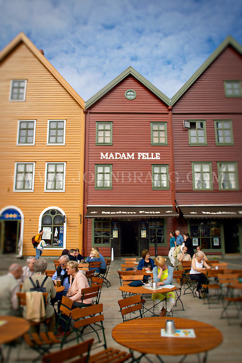 Colorful facades of buildings in Bergen, Norway, including Madam Felle restaurant, with people sitting outside at tables