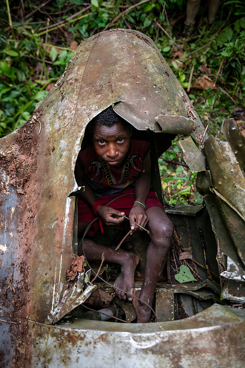 A boy sits in the tail section of an A-20 Havoc that crashed in the jungle near the Clay River in Papua New Guinea on April 5, 1944.<br /><br />(June 21, 2019)