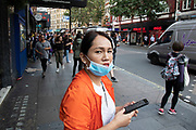 Asian woman wearing a face mask to prevent her breathing in dangerous air pollution in London, England, United Kingdom.