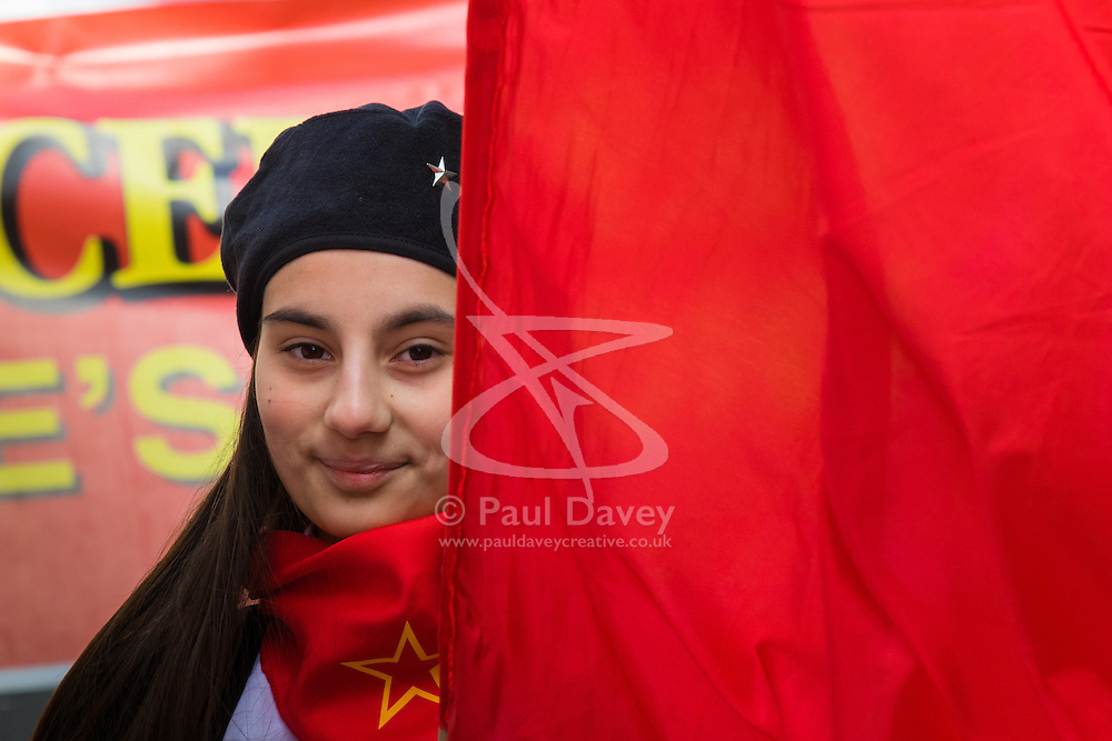 London, May 1st 2015. Hundreds of workers and Trade Unionists from across the UK are joined by Turks, Kurds and anti-capitalists as they march through London on May Day. PICTURED: A girl peers from behind her flag.