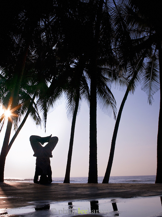 A person balances upside down while practising yoga on the beach, early in the morning in Tangalle, Sri Lanka