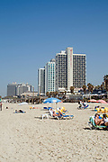 Israel, Tel Aviv, Holiday makers sunning on the beach Sea front hotels in the background