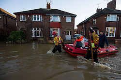 © Licensed to London News Pictures. 27/12/2015. York, UK.  Residents being rescued from their homes by members of a Mountain Rescue team on Huntingdon Road in York. Large areas of the North of England have been hit by severe flooding following unusually heavy rainfall in December. Photo credit: Ben Cawthra/LNP