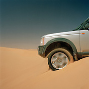 A 4x4 vechicle loses traction on the crest of a sand dune in the Sahara desert, Libya