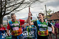"""A couple carrying the baton run on the 20th Korrika.  Hendaia (Basque Country). April 4, 2017. The """"Korrika"""" is a relay course, with a wooden baton that passes from hand to hand without interruption, organised every two years in a bid to promote the basque language. The Korrika runs over 11 days and 10 nights, crossing many Basque villages and cities. This year was the 20th edition and run more than 2500 Kilometres. Some people consider it an honour to carry the baton with the symbol of the Basques, """"buying"""" kilometres to support Basque language teaching. (Gari Garaialde / Bostok Photo)"""