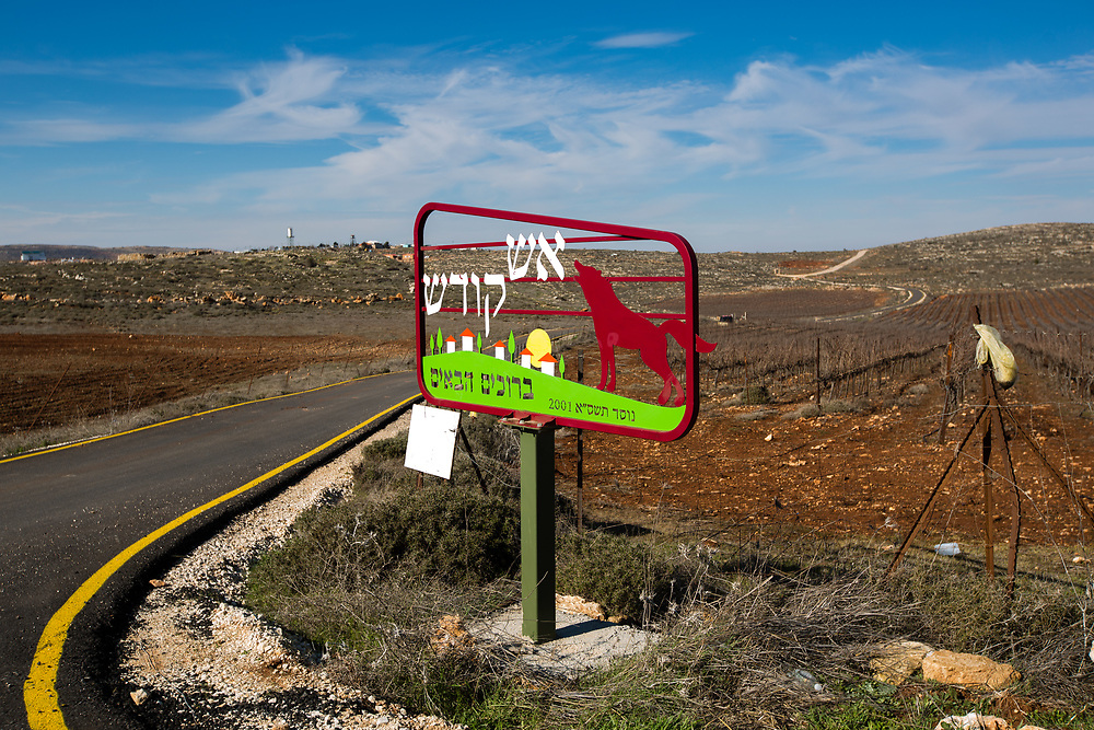 The entrance sign to West Bank Jewish outpost of Esh Kodesh, is seen in front of a winding road leading to the outpost, on January 28, 2016.