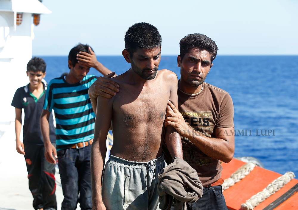 Migrants walk on the upper deck of the Migrant Offshore Aid Station (MOAS) ship MV Phoenix after being rescued from an overloaded wooden boat 10.5 miles (16 kilometres) off the coast of Libya August 6, 2015.  An estimated 600 migrants on the boat were rescued by the international non-governmental organisations Medecins san Frontiere (MSF) and MOAS without loss of life on Thursday afternoon, according to MSF and MOAS, a day after more than 200 migrants are feared to have drowned in the latest Mediterranean boat tragedy after rescuers saved over 370 people from a capsized boat thought to be carrying 600.<br /> REUTERS/Darrin Zammit Lupi <br /> MALTA OUT. NO COMMERCIAL OR EDITORIAL SALES IN MALTA