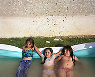 Mia (left) and Isabella Mihai (centre), play with cousin Albinuta Mihai (on right), in a paddling pool in their garden in the village of Sintesti, in Romania, early August 2006. The Kalderari roma of Sintesti are by tradition metal workers, originally making alcohol stills, pots and pans, but now dealing in scrap metal. The large profits from their business have enabled them to build large houses in the village of Sintesti, 20km from Bucharest, and to invest in fast, Western brand name cars such as BMW's, Mercedes and Porsche.