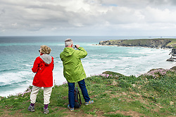 Tourists enjoy the spectacular views as they stand on the cliffs at Carnews at Bederuthan in Cornwall.