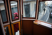 A local passenger travels in the outside of the carriage, through the central, most historic region of the city, as a long time tradition in the Lisbon's nº28 yellow tram.