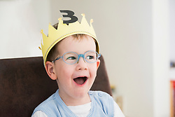 A happy boy wearing crown is surprised on his birthday, Bavaria, Germany