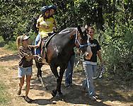 Directv Magazine -- Minda Cox (C) enjoys a afternoon horse ride at Camp Barnabas.