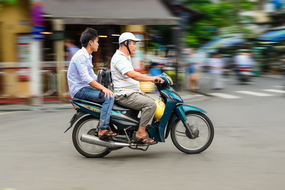Riding a motor scooter through the streets of Hanoi's Old Quarter