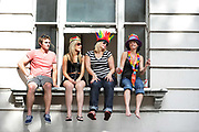 Friends sitting on a window ledge ready for the Notting Hill Carnival, London.