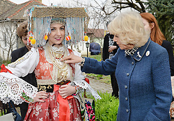 File photo dated 17/03/16 of the Duchess of Cornwall with a girl in local traditional costume, at the Bee Museum outside Novi Sad, Serbia.