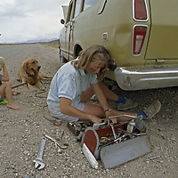Ruby Valley, Nevada. A woman works on her old truck that broke down on a desert road.