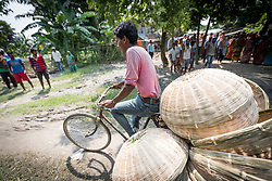 16 September 2018, Sohal Tole, Jahada rural municipality, Nepal: Gobinda Mohali shows how he rides a bike packed with baskets to the town of Biratnagar, to sell them at the market there. Basket making is a traditional skill among the Mohali (Tarai Dalits, meaning Dalits living on the plainlands of eastern Nepal), but it is only recently that they have been able to access the market and start selling their goods, in the nearby town of Biratnagar, Province 1, Nepal. Access has been made possible through support from the Nepal Evangelical Lutheran Church. Sohal Tole is a community inhabited by Santal and Dalit (Musahar) people, who find themselves as the very margin of society in Nepal. The 54 households are supported by the Nepal Evangelical Lutheran Church, as they mobilize together on disaster preparedness, income generating activities, financial governance, and mobilization on sanitation, education and entrepreneurship. The community project also receives technical support from the Lutheran World Federation World Service programme.