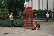 Tourists indulge in souvenir pictures near red telephone box near St. Paul's Cathedral.