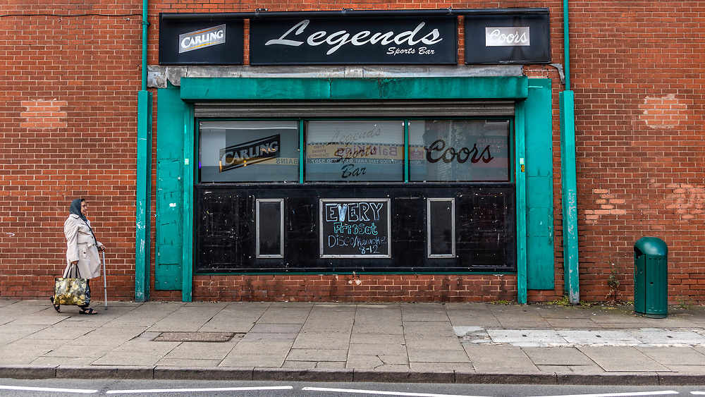 Eldery women walking past a sports bar in Tipton, northwest of Birmingham, West Midlands. It was once one of the most heavily industrialised towns in the Black Country, with thousands of people employed in the town's industries.