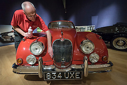 """© Licensed to London News Pictures. 29/11/2018. LONDON, UK. A technician polishes a 1959 Jaguar XK150 'S' 3.4-litre coupé (Est. GBP60,000-80,000). Preview of a sale of """"Fine Collectors' Motor Cars"""" at Bonhams, New Bond Street.  30 vehicles will be offered for sale on 1 December.  Photo credit: Stephen Chung/LNP"""
