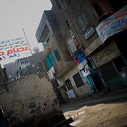 An egyptian man passes by campaign banners in Cairo's Shubra district.