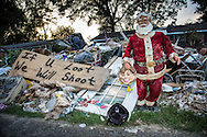 """Denham Springs, <br /> Denham Springs, Louisiana on Sept 1, 2016. Contents from homes and businesses line the street in the floods aftermath.<br />  Lisa Herbert, the owner of this house wants to be able to rebuild but said if she is required to lift her house to get a permit to rebuild it she wont have enough money to do it. The Santa out front has danced for her family for the last 13 years. 'This is his last dance"""", she said. Her son put the Hillary Clinton mask in Santa's hands. Everyday someone does something differnt with the Santa. Keeping their humor intact, Herbert said is key."""