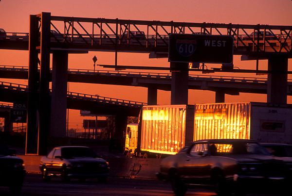 Freeway traffic passing at sunset
